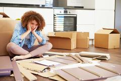 Frustrated woman putting together self assembly furniture Stock Photos