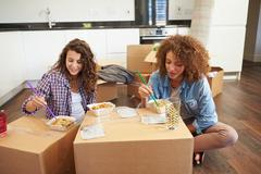 two women moving into new home enjoying takeaway meal - stock photo