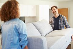 Couple carrying sofa as they move into new home Stock Photos