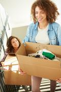 Two women moving into new home carrying box upstairs Stock Photos