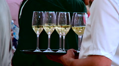Waiter holding a full glass of white wine at the celebrate reunion Stock Footage