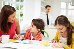 Mum helps children with homework as dad works in background Stock Photos