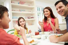 Hispanic family sitting at table eating meal together Kuvituskuvat