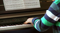 Boy musician playing piano at the concert - stock footage