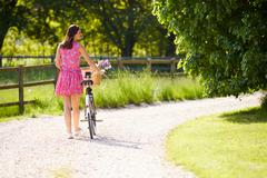 Rear view as woman pushes bike along country lane Stock Photos