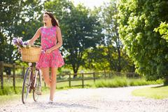 Attractive woman pushing bike along country lane Stock Photos