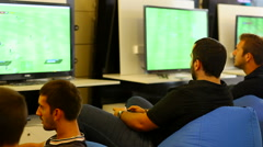 Young men playing football on a video game Stock Footage
