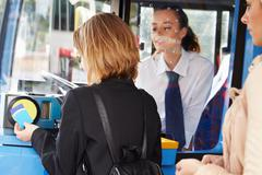 Woman boarding bus and using pass Stock Photos