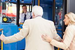 Woman helping senior man to board bus Stock Photos