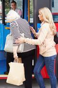 Woman helping senior woman to board bus Stock Photos
