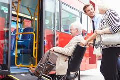 Driver helping senior couple board bus via wheelchair ramp Stock Photos