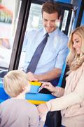 Mother and son boarding bus and using pass Stock Photos