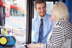 Senior woman boarding bus and buying ticket Stock Photos