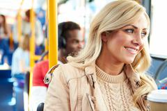 Woman enjoying takeaway drink on bus journey Stock Photos