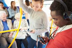 passengers using mobile devices on bus journey - stock photo