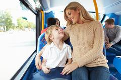 mother and son going to school on bus together - stock photo