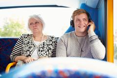 Man disturbing passengers on bus journey with loud music Stock Photos