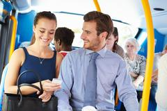 Businessman and woman looking at mobile phone on bus Stock Photos