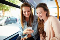 Two young women reading text message on bus Stock Photos