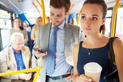 Passengers standing on busy commuter bus Stock Photos