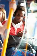 Man wearing headphones listening to music on bus journey Stock Photos