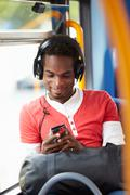 man wearing headphones listening to music on bus journey - stock photo