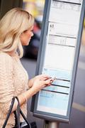 Woman at bus stop with mobile phone reading timetable Stock Photos