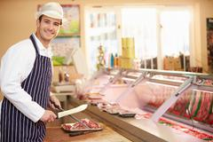 Butcher preparing meat in shop Stock Photos