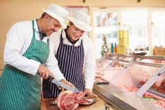 Butcher teaching apprentice how to prepare meat Stock Photos