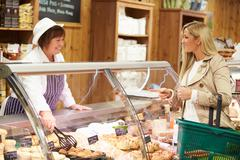 Female sales assistant serving customer in delicatessen Stock Photos