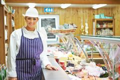 Female sales assistant in delicatessen Stock Photos