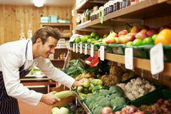 Male sales assistant at vegetable counter of farm shop Stock Photos