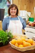 Female sales assistant at checkout of farm shop Stock Photos