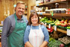 Two sales assistant at vegetable counter of farm shop Stock Photos