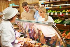 female sales assistant serving family in delicatessen - stock photo