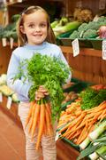 Young girl holding bunch of carrots in farm shop Stock Photos