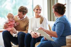 Health visitor talking to family with young baby Stock Photos