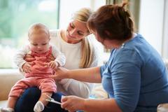 Health visitor talking to mother with young baby Stock Photos