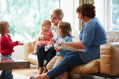 Health visitor talking to mother with young children Stock Photos