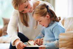 Mother and daughter reading story at home together Stock Photos
