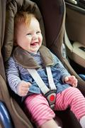 Baby sitting happily in car seat Stock Photos