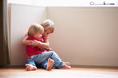 Unhappy children sitting on floor in corner at home Stock Photos