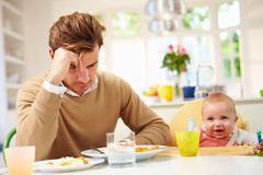 Father feeling depressed at baby's mealtime Stock Photos