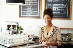 Male and female staff in coffee shop Stock Photos