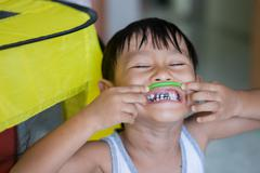 close up of happy little boy make big eye with metal crowns - stock photo