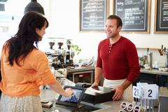 Customer paying in coffee shop using touchscreen Stock Photos