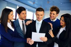 happy colleagues congratulating businessman in office - stock photo