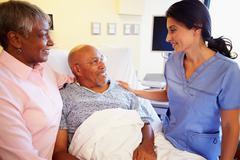 Nurse talking to senior couple in hospital room Stock Photos