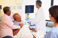 Medical team meeting with senior couple in hospital room Stock Photos