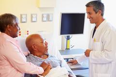 Doctor talking to senior couple on ward Stock Photos